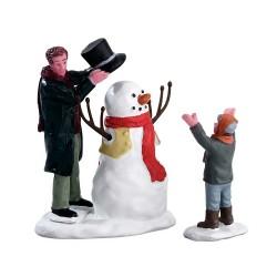Père et fils qui font un bonhomme de neige