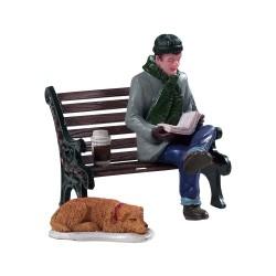 Homme qui lit un livre sur un banc